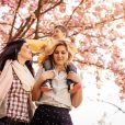 Photo of little boy and two women in the amazing nature under the cherry blossom tree